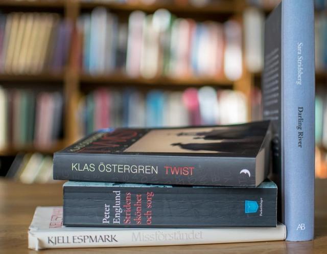 Tre liggande böcker och en stående.